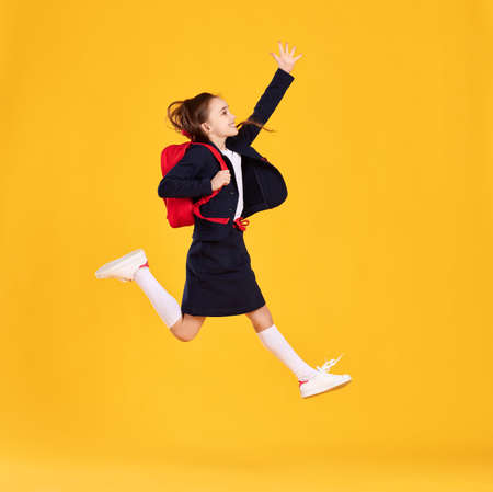Full body side view of happy preteen schoolgirl in black uniform and glasses with backpack jumping high against yellow background