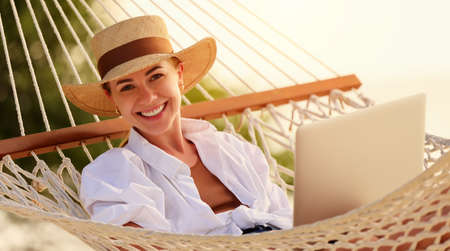 Enjoying work during summer vacation. Young happy woman, successful female freelancer in straw hat using laptop and smiling at camera while relaxing in the hammock on the tropical beach. Distance job