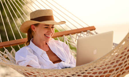 Enjoying work during summer vacation. Young happy woman, successful female freelancer in straw hat using laptop and smilingwhile relaxing in the hammock on the tropical beach. Distance job Imagens