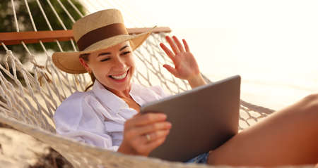 Having online conversation. Young happy successful woman wearing straw hat waving and smiling while having video call on digital tablet, relaxing in the hammock on tropical sandy beach on sunny day