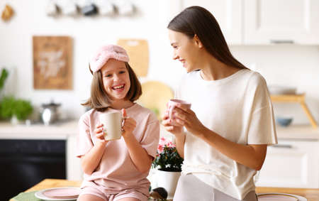 Happy time with mom. Young lovely mother and cute little daughter drinking tea and smiling while standing together in modern cozy kitchen, older and younger sister enjoying family weekend at home
