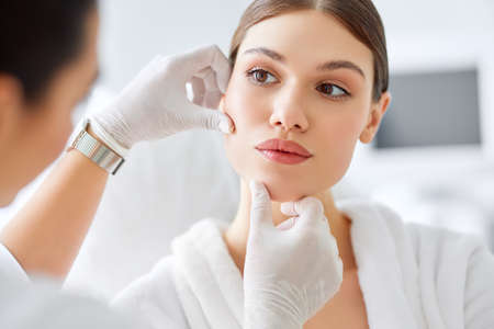 Crop anonymous cosmetologist in white gloves examining face skin of young female client before beauty procedure in salon