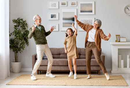 Full length of excited little preschool girl dancing having fun with active and positive grandparents. Happy child spending weekend time with family at home. Funny leisure activities concept