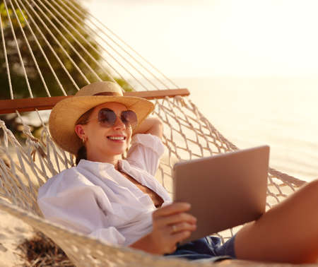 Young happy successful woman, smiling female freelancer in straw hat and sunglasses using digital tablet while lying and relaxing in the hammock on tropical sandy beach on hot sunny day. Distance work