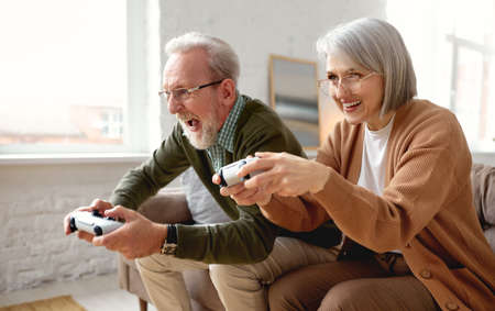 Excited concentrated senior couple husband and wife playing video console games together while sitting on couch in living room at home, laughing and having fun. Leisure time and people concept Imagens