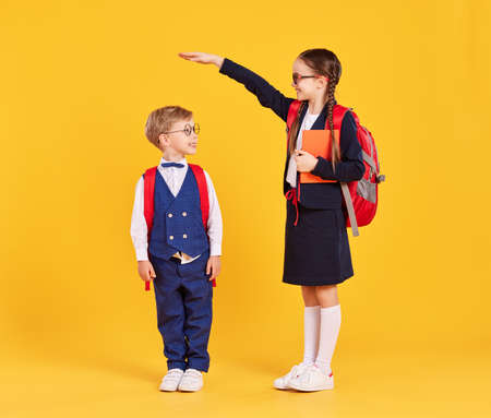 Concept of education development and growth. Happy preteen schoolgirl with backpack and book measuring height of little boy in school uniform while standing together against yellow background