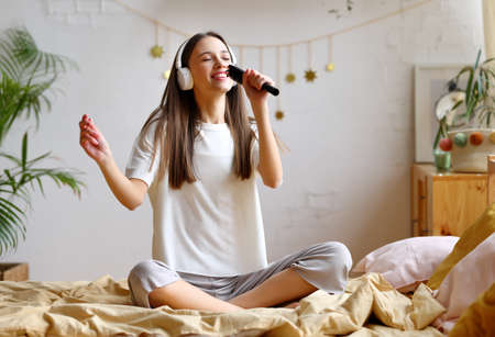 Pretending to be famous singer. Young woman in casual wear with closed eyes holding hair brush as microphone and singing her favorite song while sitting on the bed at home