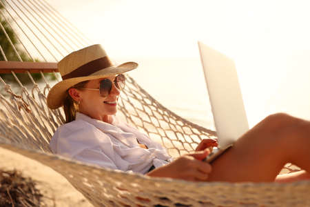 Working remotely. Side view of young happy woman, female freelancer in straw hat and sunglasses working on laptop while relaxing in the hammock on the beach at sunset. Distance job during vacation