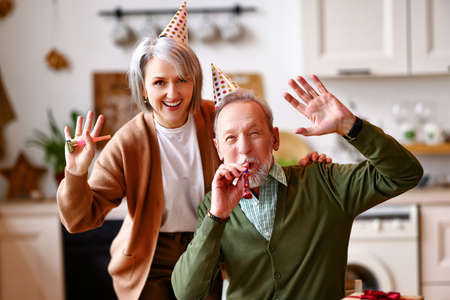 Positive elderly couple celebrating birthday at home, waving at camera. Happy senior man and woman in party hats blowing whistles and smiling, selective focus on people. Holiday celebration concept