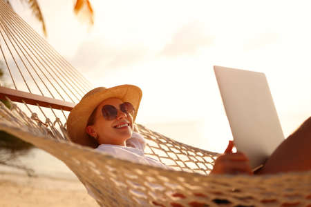 Perfect place for freelance work. Young happy woman in straw hat and sunglasses using laptop while lying in hammock on the beach at sunset, female freelancer working remotely outdoors