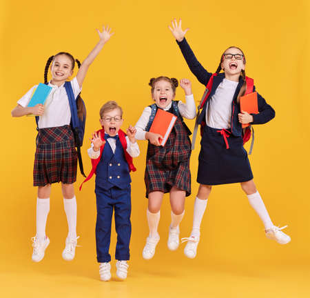 Group of funny excited classmates in school outfits with backpacks and copybooks having fun and jumping on yellow background Imagens