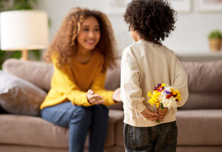 Little boy son holding present for his mommy, hiding flower bouquet behind his back while mom excited african american race woman sitting on sofa and waiting, selective focus o child. Mothers day celebration