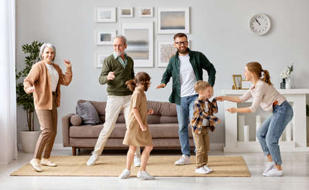 Full length of big happy family grandparents, father, mother and two kids siblings dancing and having fun in the living room at new home, spending weekend time together. Funny leisure activities