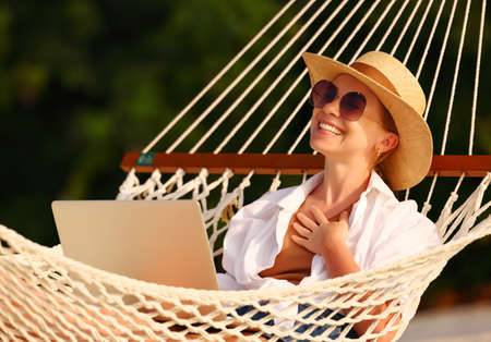 Working from everywhere. Young satisfied woman, successful female freelancer in straw hat and sunglasses using laptop and smiling while relaxing in the hammock on the beach, selective focus Imagens