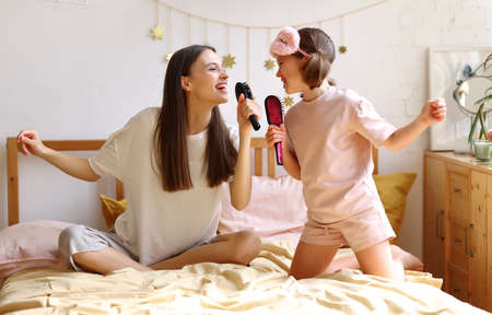 Two happy girls pretending to be famous singers, overjoyed younger and older sister with hairbrush as mic singing while sitting on the bed. Young mom and cute little daughter having fun at home