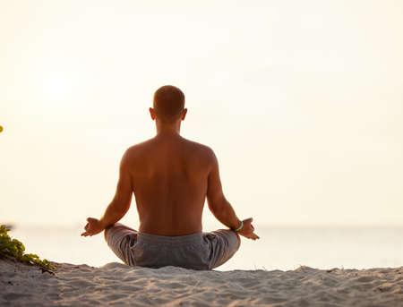 Back view of male sitting in Padmasana while meditating alone on seashore against sky in sundown light