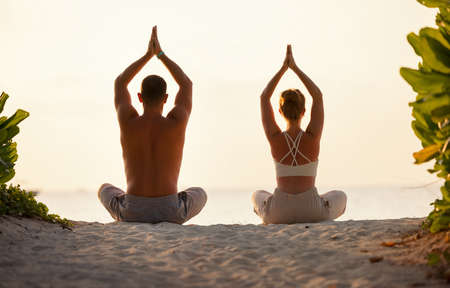 Back view of man and woman in sportive clothes practicing Lotus pose with Namaste hands above heads on coastline
