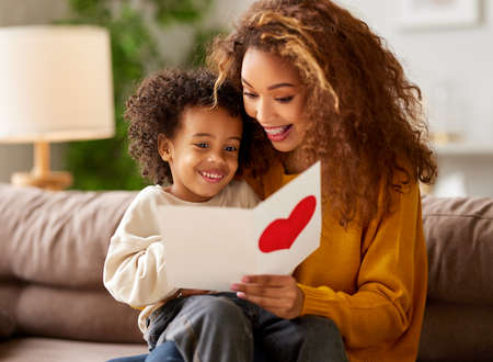 Cute little boy son congratulating his mom happy mixed race woman with Mothers day, giving her handmade greeting postcard with red heart while sitting together on sofa at home. Family holidays concept