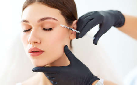 Crop anonymous cosmetologist in gloves applying injection to face of young female patient during skin care lifting procedure in beauty clinic Imagens