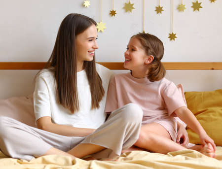 Morning with mom. Young happy mother and cute little daughter wearing pajamas having good talk in bed at home, cheerful older and younger sister spending time together in bedroom