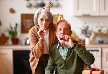Happy beautiful senior couple celebrating birthday at home, elderly man and woman wearing party hats embracing, blowing whistles and looking at camera. Celebration and holiday concept Imagens