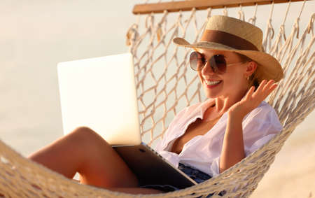 Having online conversation. Young happy successful woman wearing straw hat waving and smiling while having video call on laptop, relaxing in the hammock on tropical sandy beach on sunny day Imagens