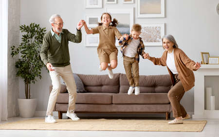 Full length of two excited kids siblings having fun playing with active and positive grandparents in the living room at home, enjoying weekend time with energetic senior old grandma and grandpa Imagens
