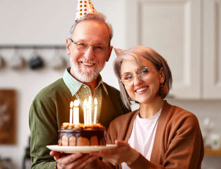 Beautiful senior couple in party hats celebrating birthday and anniversary together at home, holding chocolate cake, hugging and smiling while standing in modern kitchen. Family celebration concept Imagens