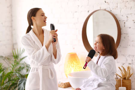 Side view of young woman and little daughter in white bathrobes holding hairbrushes in hands as microphones and singing together while enjoying beauty procedure at home 版權商用圖片