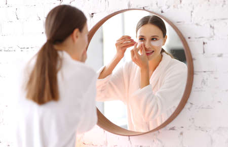 Happy young female in white bathrobe applying moisturizing patches under eyes in front of mirror in bathroom