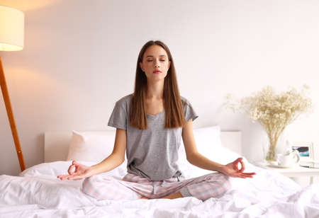 Full body young female in pajama sitting in Lotus pose on bed and meditating with closed eyes in morning at home 版權商用圖片