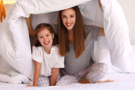 Optimistic family: young mother and daughter smiling and looking at camera while sitting under warm duvet on comfortable bed at home 版權商用圖片