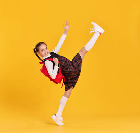 Full body side view of smiling elementary schoolgirl in checkered dress with backpack raising leg and arm while getting hurry to school against yellow background