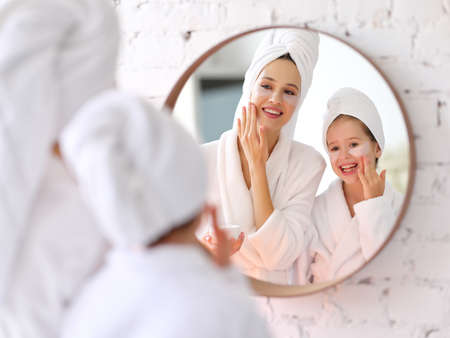 Smiling young woman and little daughter in white bathrobes and towels with eyes patches on faces looking at mirror during skincare procedure at home 版權商用圖片