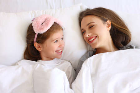 From above delighted girl and and young woman smiling and looking at each other while lying under warm duvet in morning at home