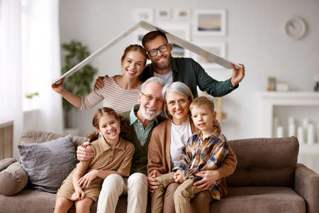 Big happy family, grandparents, mother, father with little kids son and daughter celebrating relocation in new home, sitting on the coach under paper roof and smiling at camera. Mortgage loan concept