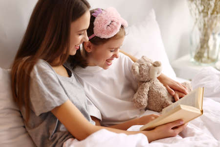 Cheerful mother hugging daughter while resting on bed and reading book together in weekend morning at home