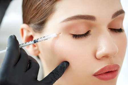 Crop anonymous cosmetologist in gloves applying injection to face of young female patient during skin care lifting procedure in beauty clinic 版權商用圖片