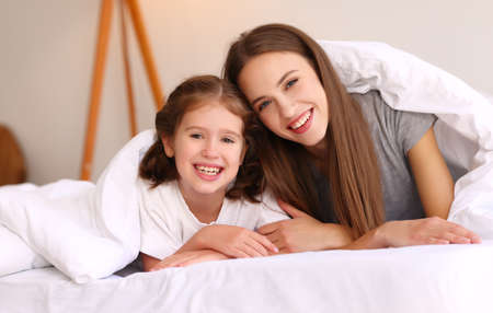 Optimistic family: young mother and daughter smiling and looking at camera while lying under warm duvet on comfortable bed at home 版權商用圖片
