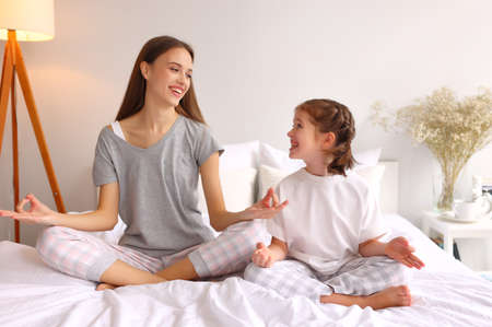 Full body family: young woman and girl sitting in Lotus pose and looking at each other with smile while meditating on bed at home