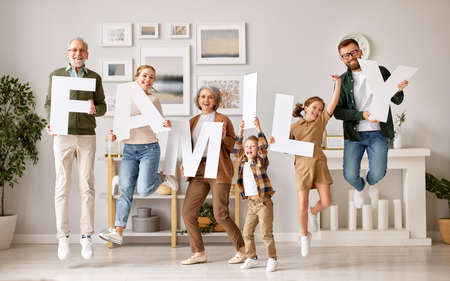Celebrating relocation in new modern home. Excited grandparents, mother and father with little kids holding word FAMILY and jumping with happiness, full length. Mortgage and real estate concept 版權商用圖片