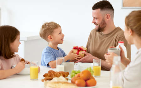 Best dad ever. Cute happy little boy son giving daddy wrapped gift box for Fathers day or birthday while eating breakfast with family in kitchen at home. Family holidays concept
