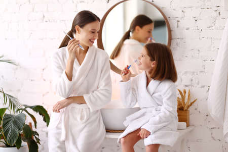 Side view of happy young woman with little daughter in white bathrobes brushing teeth together in bathroom and enjoying morning time together