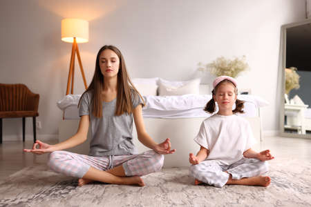 Young woman and girl with closed eyes breathing and meditating while sitting in Lotus pose near bed in morning at home