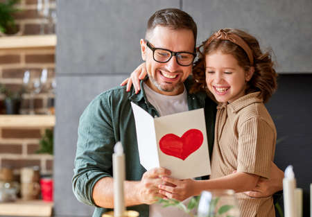 Portrait of happy family father with excited child daughter hugging smiling at camera while celebrating Fathers day together at home. Little girl congratulating giving dad homemade greeting postcard