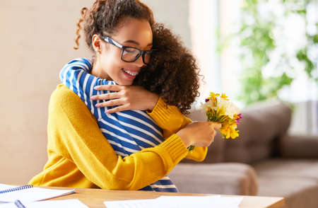 Little child son congratulating mom with Mothers day or birthday, giving her fresh flower bouquet. Happy mixed race woman mother embracing with child while working at home. Family holidays concept 版權商用圖片