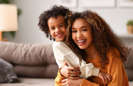 Cute little boy son congratulating his mom happy mixed race woman with Mothers day, hugs her and laughs while sitting together on sofa at home. Family holidays concept 版權商用圖片