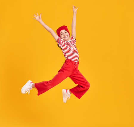 Full body of energetic child girl in striped shirt and red hat and pants raising arms and jumping high against yellow background
