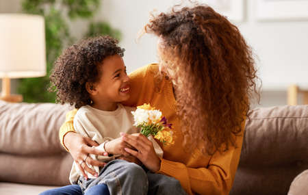 Excited boy little son congratulating his mom happy mixed race woman with Mothers day and giving her flower bouquet, they hugging and laughing while sitting on sofa at home. Family holidays concept