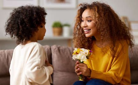 Excited boy little son congratulating his mom happy mixed race woman with Mothers day and giving her flower bouquet, they smiling while sitting on sofa at home. Family holidays concept